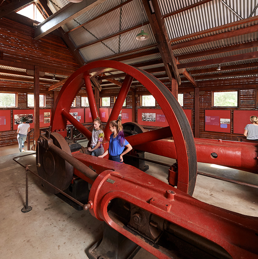 A large steam engine in a museum shed with youth engaging with the museum