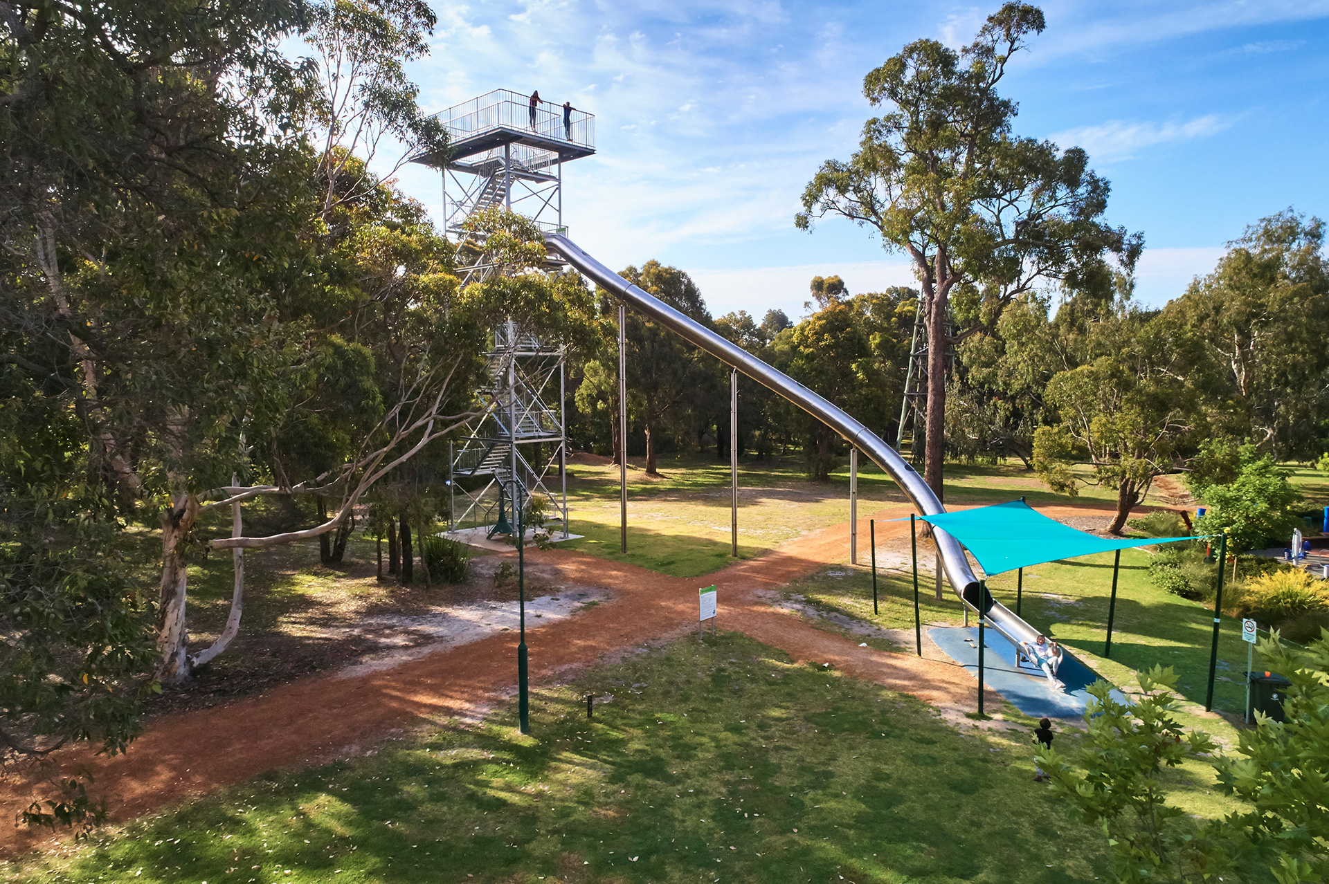 Very tall lookout tower and tube slide surrounded by trees
