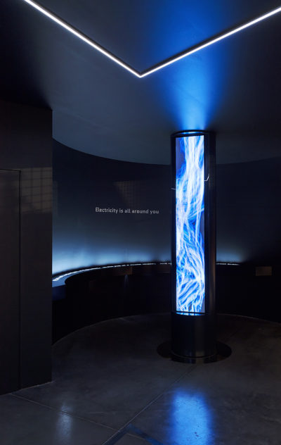 dark room with large screen showing electrical bolts