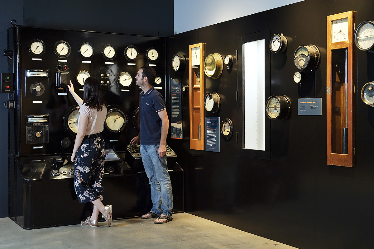 couple look at historical dials in electrical display