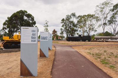 interpretative signage along pathway with rail display in the background