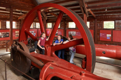 youth looking at large steam engine display