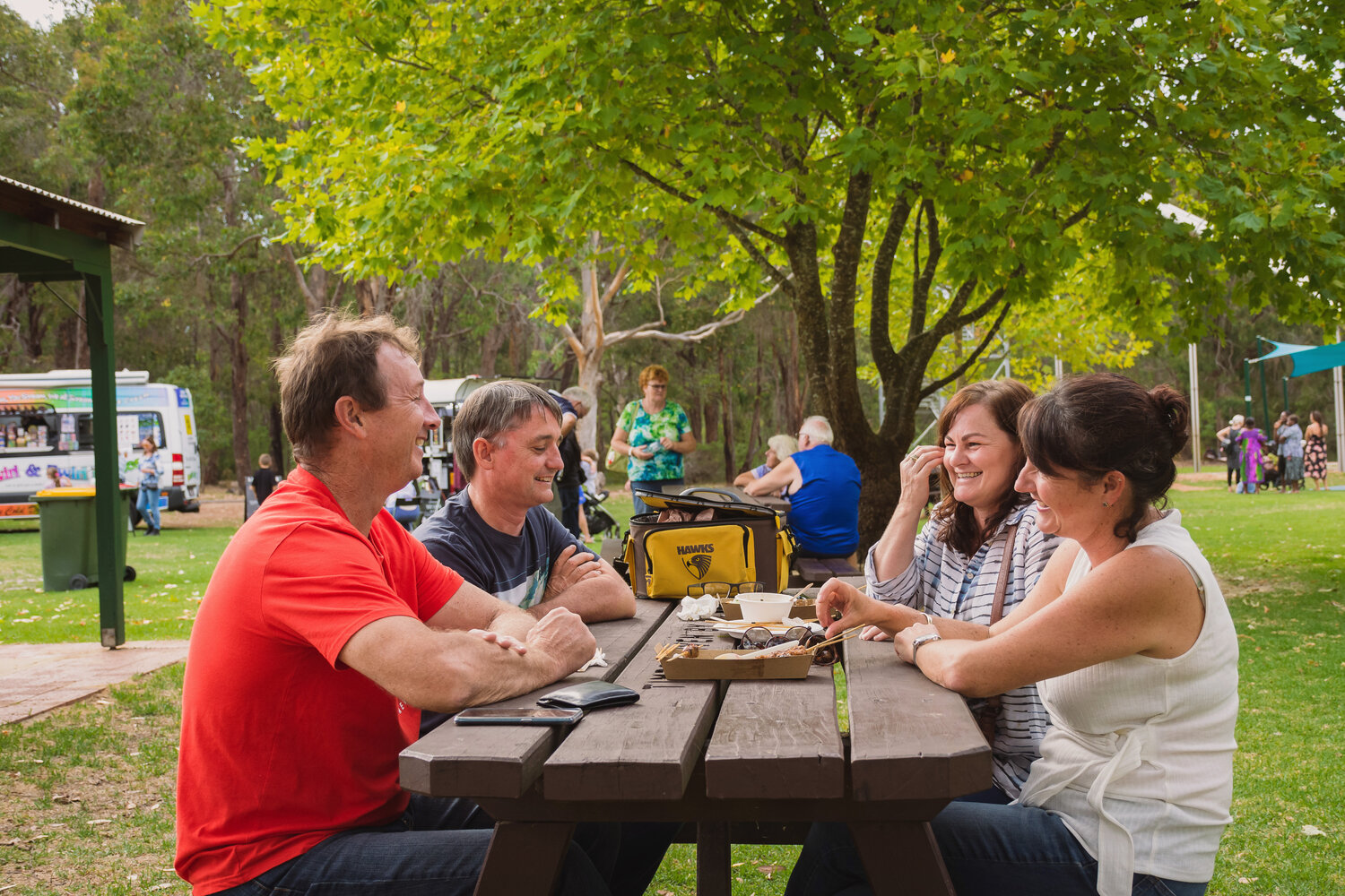 Four adults sitting at a picnic table enjoying some food